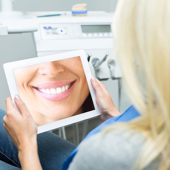 Woman looking at virtual smile design image on tablet computer