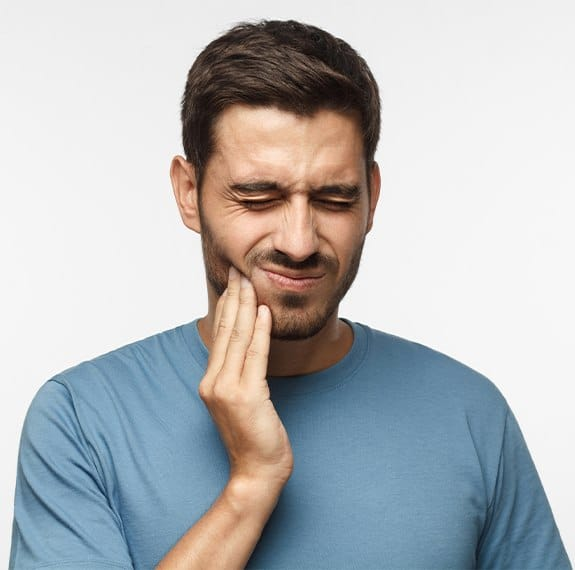 Man in need of tooth extraction holding jaw in pain
