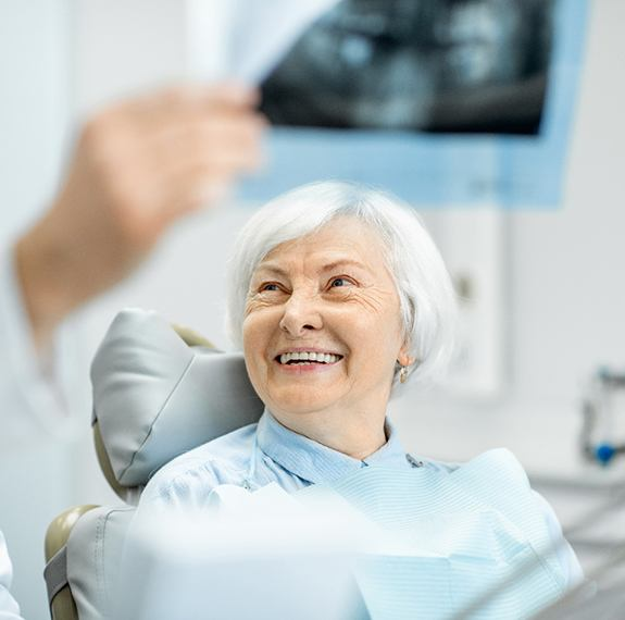 An older woman seated in the dentist's chair listening to her dentist go over her X-Rays and the cost of dental implants in Fairfax