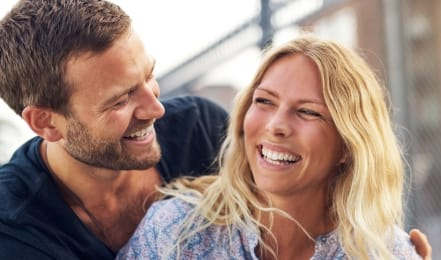 Man and woman with healthy smiles thanks to periodontal therapy