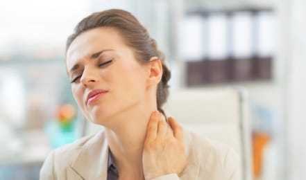 Woman in need of T M J therapy holding neck in pain