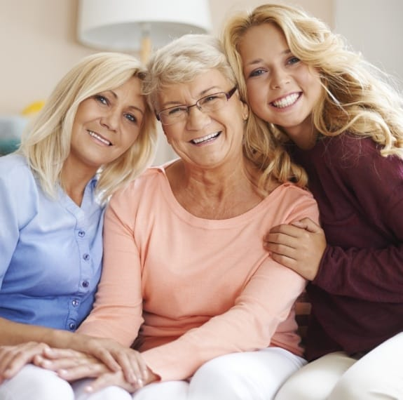 Three generations of women sharing healthy smiles after receiving dental services in Fairfax