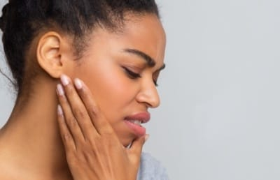 Woman with jaw pain holding her cheek