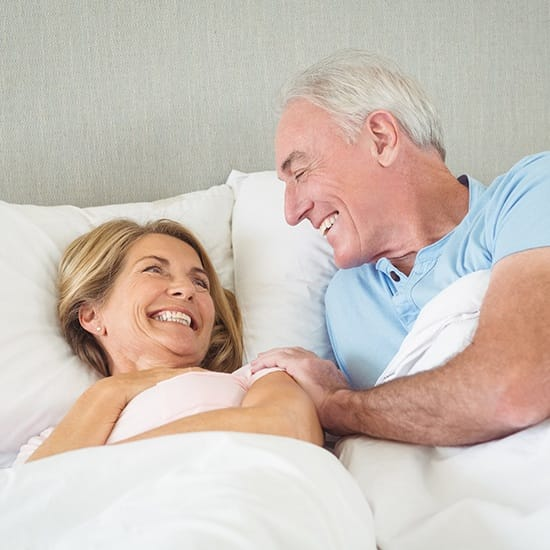 Man and woman waking feeling rested thanks to sleep apnea therapy
