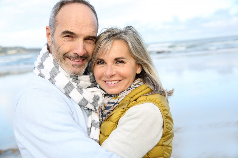 Mature couple smiling on beach together