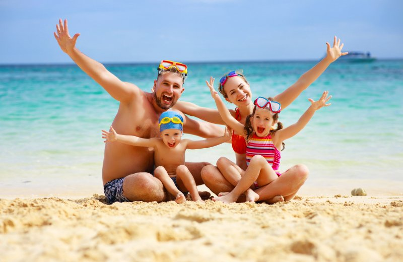 family posing on the beach during summer vacation